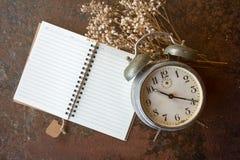 Retro klocka och anmärkning med den vita blomman som ligger på den rostiga tabellen Royaltyfria Bilder