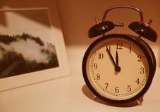 Retro klocka- och bildram på serveringsbordet Arkivbild