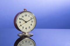 Retro klocka på trevlig blå bakgrund med reflexion Fotografering för Bildbyråer