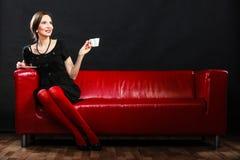 Retro kobieta trzyma herbacianej filiżanki obsiadanie na kanapie obraz stock