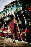 Retro kobieta z walizką przy dworcem. Zdjęcie Royalty Free