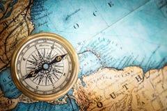 Retro kompass för gammal tappning på forntida översiktsbakgrund royaltyfri foto