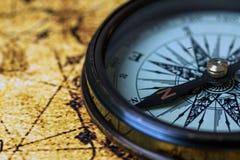 Retro kompass på antik världskarta Fotografering för Bildbyråer