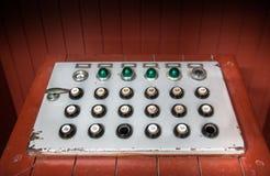 Retro kontrollbord med knappar, kulöra ljus och strömbrytare Arkivfoton