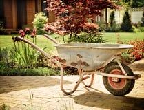 Retro kruiwagen in de tuin wordt opgeslagen die Stock Foto