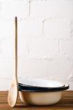 Retro kuchennych naczyń drewniana łyżka i starzy emaliowi puchary w rusti Obrazy Stock