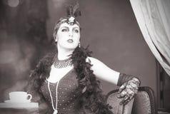 Retro kvinna20-tal - 30-tal som sitter med kopp te Fotografering för Bildbyråer