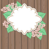 Retro label with pink flowers over wood Royalty Free Stock Photography