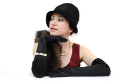 Retro lady watching. Young beautiful lady in black retro hat and gloves, wearing pearl necklace and bracelet, sitting and looking aside, presumably watching Stock Photo