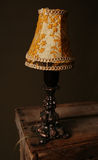 Retro lamp. Old lamp and lampshade standing on wooden box. retro light in dark brass stock photo