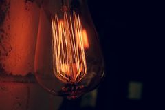 Retro lamp on a brick wall close-up. Retro lamp on the brick wall, retro lamp close up, filament in the lamp, filament close-up, light in the dark, lights the Royalty Free Stock Image