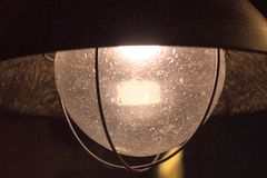 Retro lamp with glass with air bubbles in the glass. metal base, glass and dim light for cozy evenings royalty free stock photos