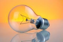 Retro lampadina d'annata con sul fondo giallo-chiaro caldo della tinta Fotografie Stock