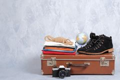 Retro leather suitcase with travel accessories on grey background. Stack of clothes, film photo camera, suede shoes, globe. Travel. Concept, banner mockup with stock photo