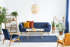 Retro- Lehnsessel mit Holzrahmen und bunte Kissen auf einem Marineblausofa in einem vibrierenden Wohnzimmerinnenraum mit Grünpfla stockbild