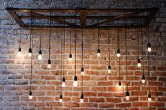 Old red brick wall with bulb lights lamp. Retro light bulbs hang on retro cords. Old red brick wall with bulb lights lamp stock photography