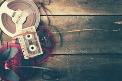 Retro ljudsignal rullar och kassett på trätabellen med kopieringsutrymme royaltyfri fotografi