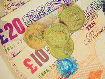 Retro look Pounds. Vintage looking Detail of British Pounds banknotes and coins Stock Photo