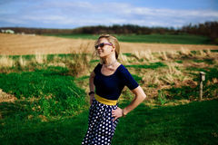 Retro Looking Blonde Women with Sunglasses Standing in a Field Stock Images
