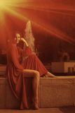 Retro looking photo of women in red dress sitting near fountain Royalty Free Stock Photo