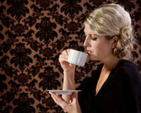 Retro looking woman drinking tea or coffee Stock Photography