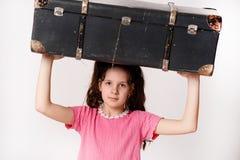 Retro- Mädchen, das einen Koffer auf Kopf hält Stockbild