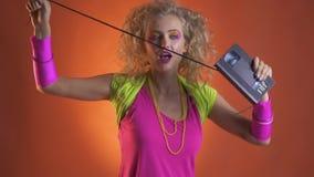Retro- Mädchen mit buntem bilden zerreißt Band von der Kassette stock video