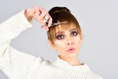 Retro- Mädchen mit elegantem Make-up auf Gesicht Retro- Mädchenschnitthaar mit Scheren Stockfoto