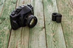 Retro macchina fotografica con il film sulla tavola di legno verde Fotografia Stock