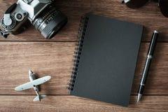 Retro macchina fotografica con il taccuino nero su fondo di legno Fotografia Stock Libera da Diritti