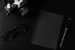 Retro macchina fotografica con il taccuino nero sullo PS nero della copia e del fondo Immagini Stock