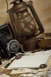 Retro macchina fotografica, lampada di cherosene e vecchie foto fotografie stock
