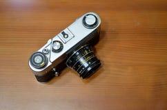 Retro macchina fotografica sul fondo di legno della tavola Fotografia Stock