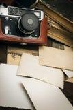 Retro macchina fotografica tranquilla ed alcune vecchie foto sul fondo di legno della tavola Fotografia Stock