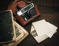 Retro macchina fotografica tranquilla ed alcune vecchie foto sul fondo di legno della tavola Fotografie Stock