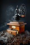 Retro macinacaffè con i fagioli e fumo isolato sul nero Fotografia Stock Libera da Diritti