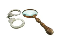 Retro Magnifying Glass and Handcuffs Royalty Free Stock Images