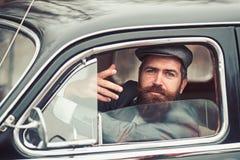 Retro man in retro car showing communicative gesture. stock image