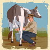 Retro man som mjölkar kon Royaltyfri Fotografi