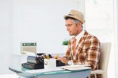 Retro man in straw hat typing on typewriter Royalty Free Stock Images