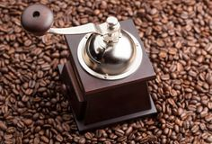 Manual coffee grinder on a background of coffee beans Stock Photos