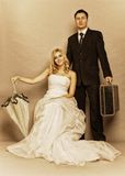 Retro married couple bride groom vintage photo. Wedding day. Portrait of married retro couple blonde bride with umbrella and groom with suitcase. Full length Stock Photo