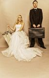 Retro married couple bride groom vintage photo. Wedding day. Portrait of married retro couple blonde bride with umbrella and groom with suitcase. Full length Royalty Free Stock Photo