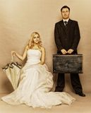 Retro married couple bride groom vintage photo. Wedding day. Portrait of married retro couple blonde bride with umbrella and groom with suitcase. Full length Royalty Free Stock Images