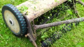 Retro mechanical lawnmover moves stock footage