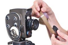 Retro mechanical movie camera and film in hands operator Stock Photos