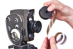 Retro mechanical movie camera and film strip in hands operator Royalty Free Stock Image