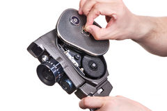 Retro mechanical movie camera in hands of operator opening cover Stock Photos