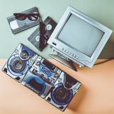 Retro media technologies. Entertainment 80s. Black white lamp TV, tape recorder, video cassette, 3d glasses. On a green pastel yellow background. Top view. Flat stock photos