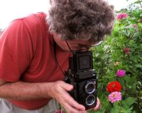 Retro Medium Format Photography. Photo of middle aged man taking a photo in a flower garden with a twin reflex camera. This type of camera became popular in 1929 stock image